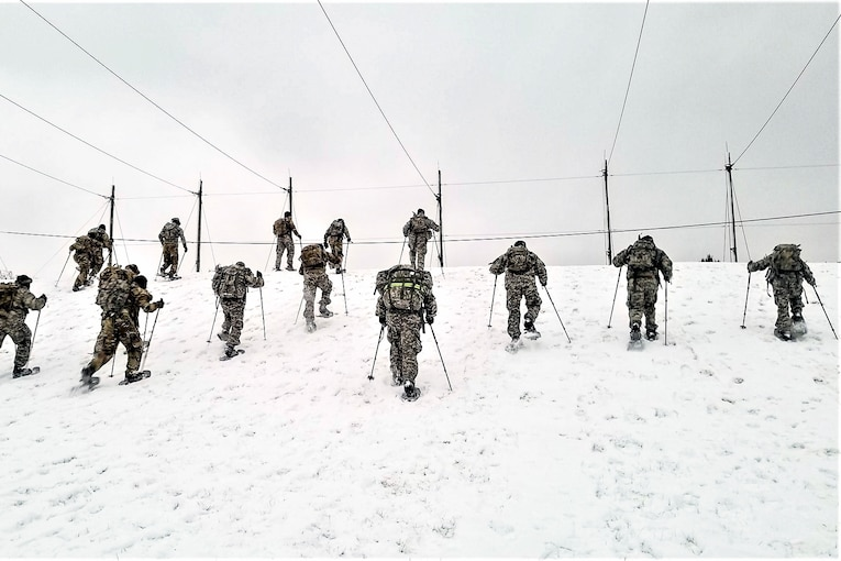 Soldiers snowshoe up a hill.