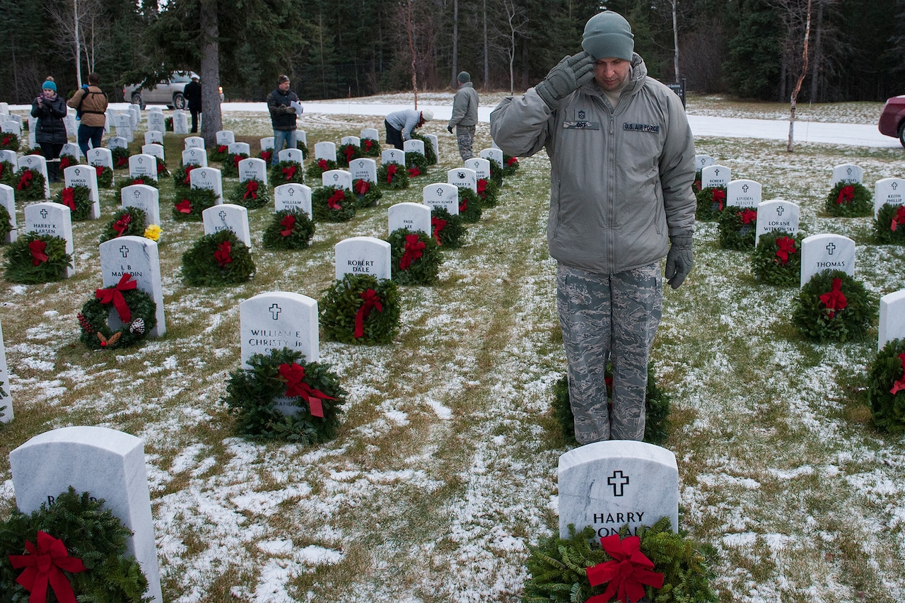 An Airman salutes after placing wreath on a grave at Arlington National Cemetery.