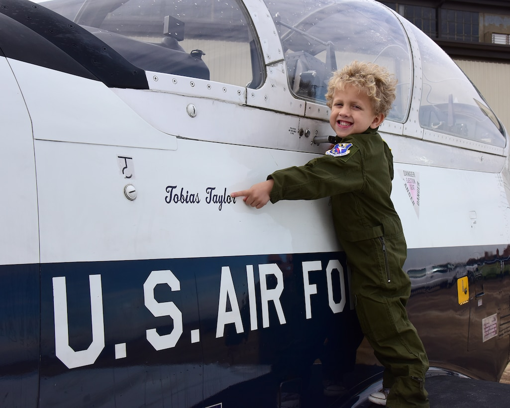Tobias Taylor, Pilot for a Day, points to his name on a T-6 Texan II on the flight line, Dec. 6, 2018, at Columbus Air Force Base, Mississippi. While unable to actually fly in an aircraft, Tobias and his family enjoyed many aspects of Columbus AFB including displays of all three 14th Flying Training Wing training aircraft, a personalized tour of the fire department, time in the T-6 flight simulator, and more. (U.S. Air Force photo by Elizabeth Owens)