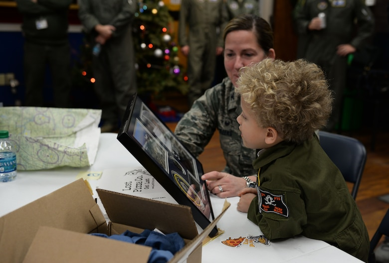 Tobias Taylor, Pilot for a Day, looks at a plaque of his hero shot and coin commemorating his time on base with Col. Samantha Weeks, 14th Flying Training Wing commander, Dec. 6, 2018, on Columbus Air Force Base, Mississippi. Weeks presented the plaque during lunch, thanking Tobias and his family for visiting Columbus AFB. (U.S. Air Force photo by Airman Hannah Bean)