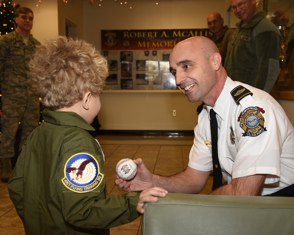 Shawn Ricchuito, 14th Civil Engineer Squadron Fire Chief, presents Tobias Taylor, Pilot for a Day, a baseball signed by all members of the fire department, Dec. 6, 2018, on Columbus Air Force Base, Mississippi. Tobias and his family enjoyed many aspects of Columbus AFB including a personalized tour of the fire department, time in the T-6 flight simulator, and more. (U.S. Air Force photo by Melissa Doublin)