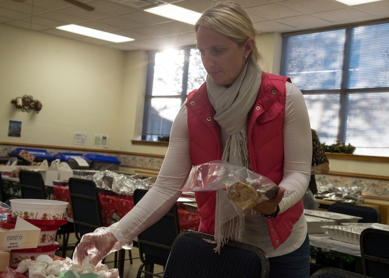 Kelli Thomas, spouse of U.S. Air Force Col. Steven Thomas, 97th Civil Engineer Squadron commander, places cookies in a bag, Dec. 11, 2018, at Altus Air Force Base, Okla.
