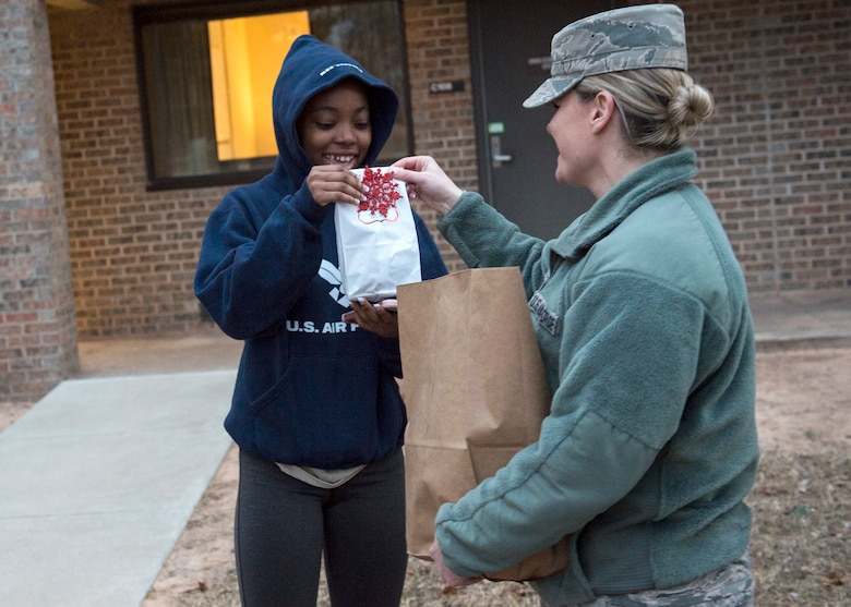 U.S. Air Force Maj. Johanna O'Toole, 97th Logistics Readiness Squadron commander, hands cookies to U.S. Air Force Airman Monique Bolton, 97th LRS vehicle maintenance journeyman, Dec. 11, 2018, at Altus Air Force Base, Okla.