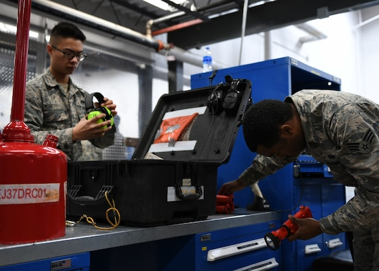 Airman 1st Class Alexander Moreto, a 28th Aircraft Maintenance Squadron hydraulic systems apprentice, left, inspects a tool kit prior to checking it out during a shift change at Ellsworth Air Force Base, S.D., Dec. 4, 2018. Tool kits are inspected to ensure every piece is intact when it is checked out and returned. (U.S. Air Force photo by Senior Airman Denise Jenson)