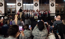 Parents crowd to take photos of the Scott Youth Center choir as they perform their holiday concert during the Holiday Party and Tree Lighting Ceremony, Dec. 7, 2018, at Scott Air Force Base, Illinois. On-base and off-base organizations coordinated to pull of the event.