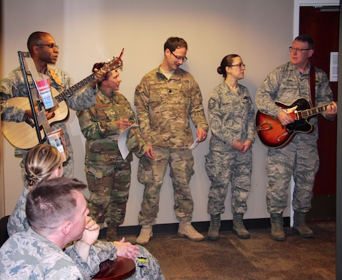 At left, Col. Lance Turner, the 932nd Mission Support Group's multi-talented commander, along with other officers and enlisted leadership, stopped by the 932nd Force Support Squadron customer service waiting area around lunch time in the headquarters building to share some holiday songs Dec 2, 2018, at Scott Air Force Base, Illinois. They sang various melodies during the Unit Training Assembly to help Airmen pass the time in the line. The other highly talented guitar player at far right is Master Sgt. Tony Loving, who has been a vocalist and guitarist in a band for many years.  All the action was captured for historical documentation by Master Sgt. Christopher Parr on his tripod and video camera just outside the frame. (U.S. Air Force photo by Lt. Col. Stan Paregien)