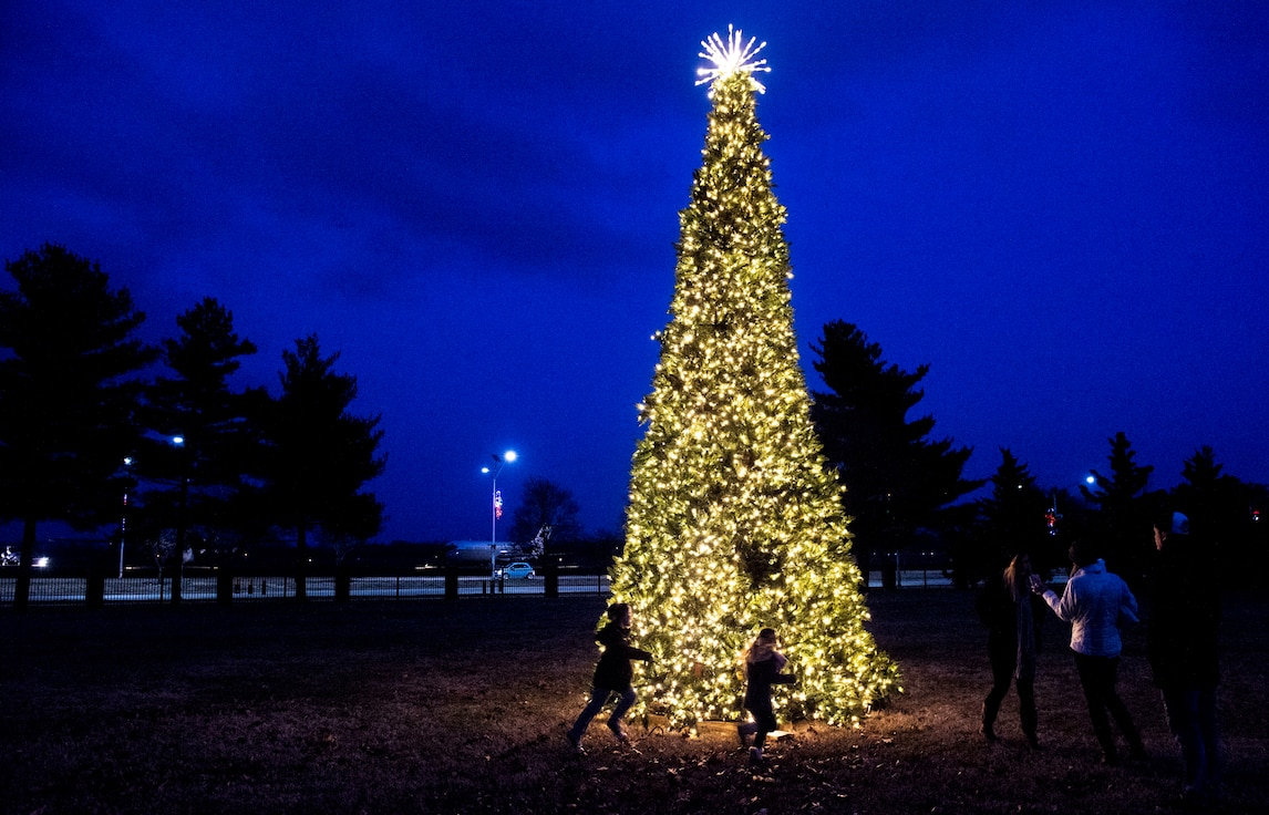"Staff Sgt. Joseph Tharp, 375th Operational Support Squadron aircrew flight equipment technician, and his family take photos near the Scott Event Center tree during the Holiday Party and Tree Lighting Ceremony, Dec. 7, 2018, at Scott Air Force Base, Illinois. ""The most memorable moment was seeing the kids' faces light up when Santa and Mrs. Claus walked through the door,"" said Tharp."