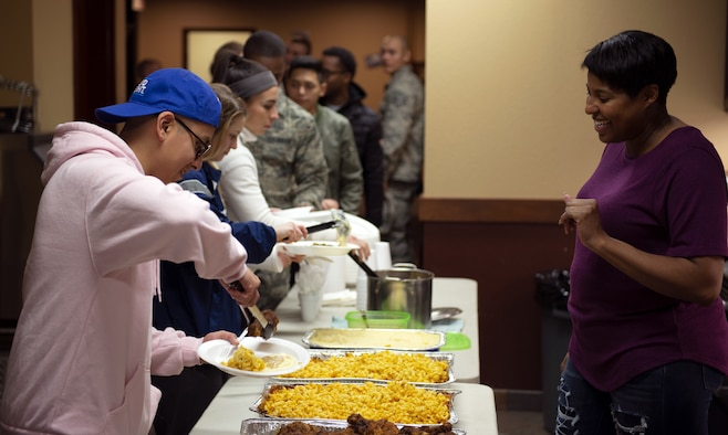 """Tech. Sgt. Aisha Terry, 375th Security Forces Squadron NCO in-charge of the Visitor Control Center, greets Airmen during a weekly dorm dinner Dec. 11, 2018, held at the Belleville Dorm Dayroom on Scott Air Force Base, Illinois. The 375th Air Mobility Wing chapel staff manages a weekly """"dorm dinner"""" program that allows organizations to provide home cooked dinners for Airmen.  Along with yummy meals, the effort gets them out of the dorms to socialize and interact with each other and many members of the community both on and off base."""