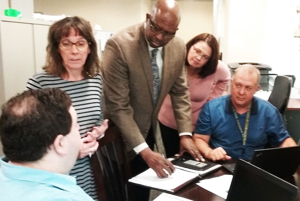 Members of AFIMSC's Financial Operations Division discuss a plan for certifying the time cards of nearly 700 Tyndall Air Force Base employees affected by Hurricane Michael. From left to right, Jason Schneider, Linda Alcala, Charles Hendricks, Ellen Lounsberry, and Rick Baltes. (U.S. Air Force Photo by Ed Shannon)