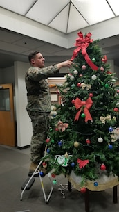 Staff Sgt. Nicholas Hensley, Base Operations Chief, adds the final touch to the Christmas Tree located in Base Headquarters aboard Marine Corps Logistics Base Barstow, Calif., Dec. 6.