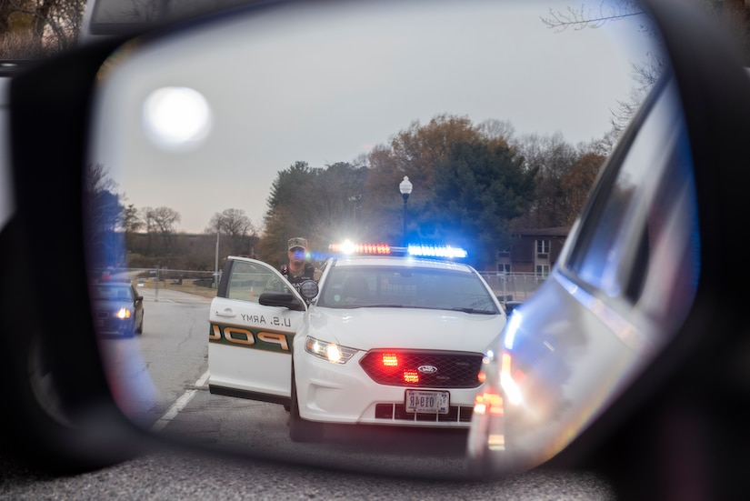 Specialist Rojas and his police car in the side mirror of a vehicle