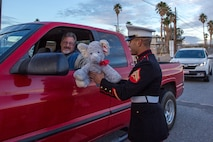 Corporal Manuel Ruiz, Fleet Support Division mechanic, receives a toy donation, in support of Toys for Tots, from Harrison Rogers at the front gate aboard Marine Corps Logistics Base Barstow, California, Dec. 4.