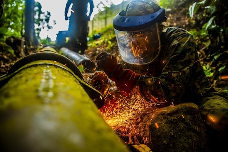 U.S. Marine Staff Sgt. Immanuel Garcia, a metal worker with Special Purpose Marine Air-Ground Task Force - Southern Command, begins cutting sections of a broken water pipe in Trujillo, Honduras, Sept. 19, 2018.