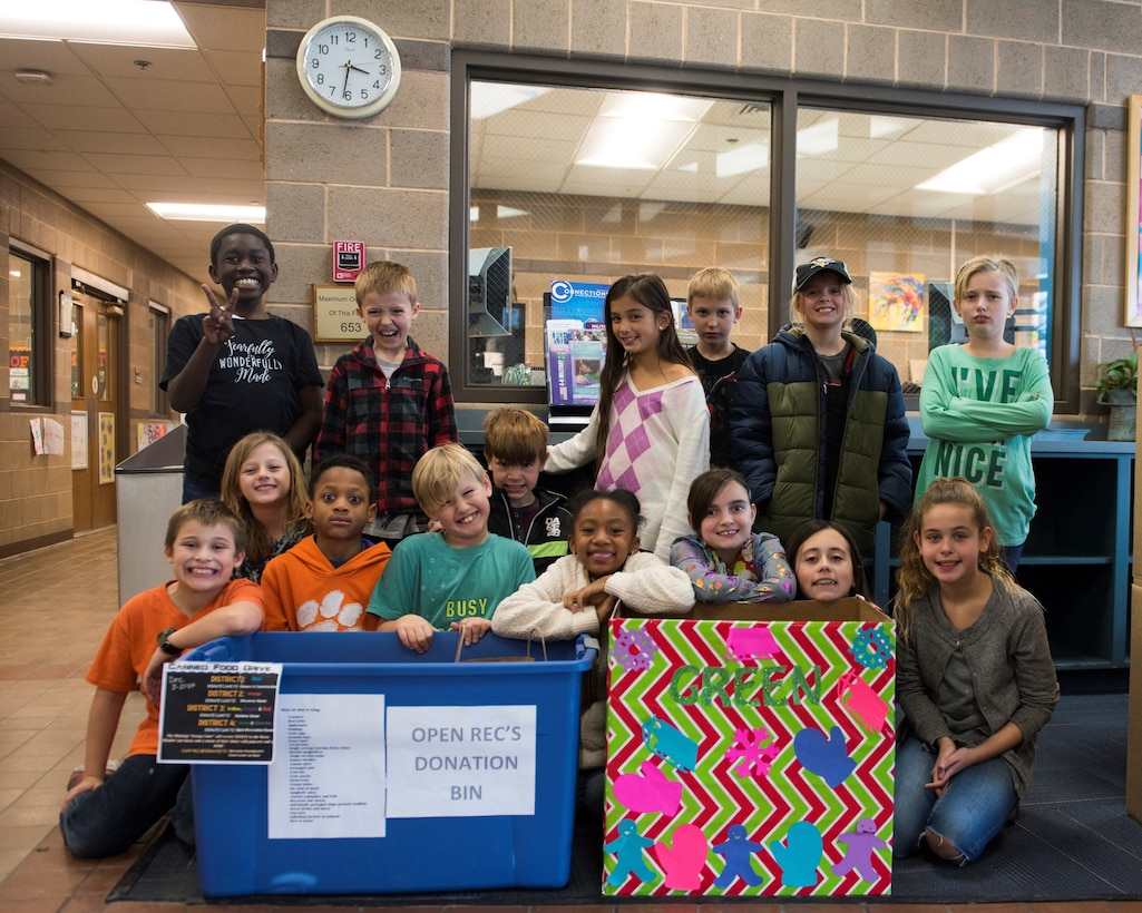Image of Youth Center children posing for a photo behind food drive donation bins, Dec. 13, 2018, at Mountain Home Air Force Base, Idaho. The Youth Center is holding a food drive to give canned and non-perishable food items to families in need. (U.S. Air Force photo by Senior Airman Alaysia Berry)