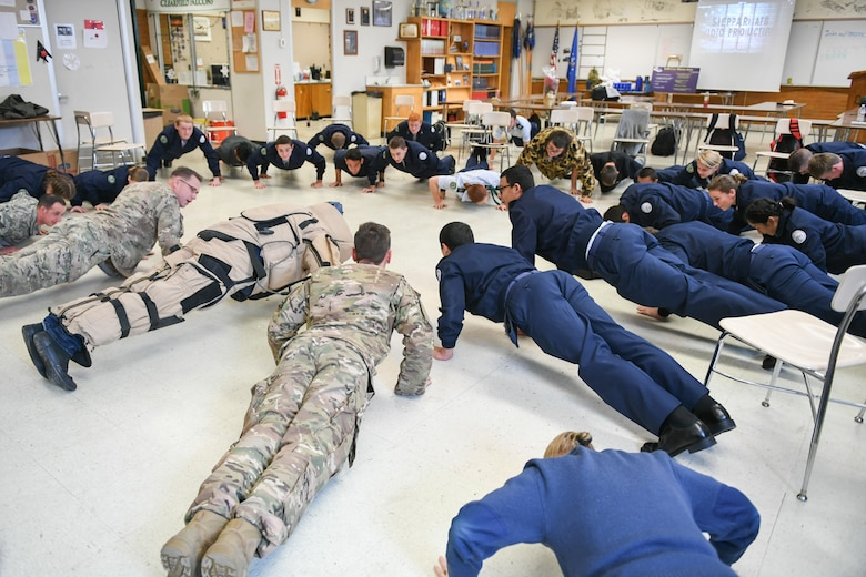 Airmen from Hill's explosive ordnance disposal team and students from Clearfield High School's Junior ROTC class perform push-ups as part of an Air Force Reserve recruiting event Dec. 12.