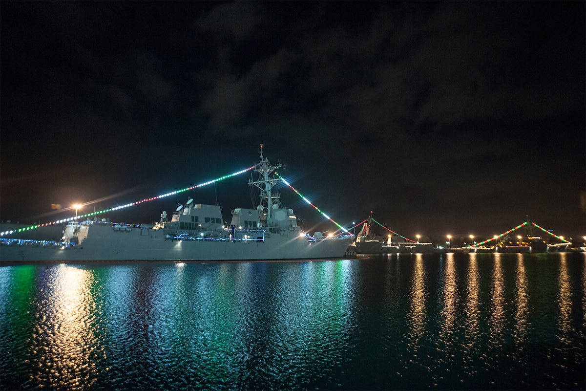 A Navy ship is decorated with Christmas lights.