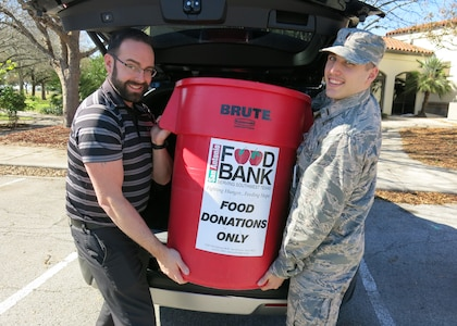 Jason Wheeler, 359th Medical Operations Squadron physical therapist, left, and 2nd Lt. Michael Ehlen, 12th Training Squadron student pilot, place a container of nonperishable food items into a vehicle for eventual transport to the San Antonio Food Bank Dec. 10, 2018, at Joint Base San Antonio-Randolph. The 359th MDOS Physical Therapy Flight is leading two drives during the holiday season: One of them will benefit the San Antonio Food Bank, while the other will provide relief to the victims of Hurricane Michael.