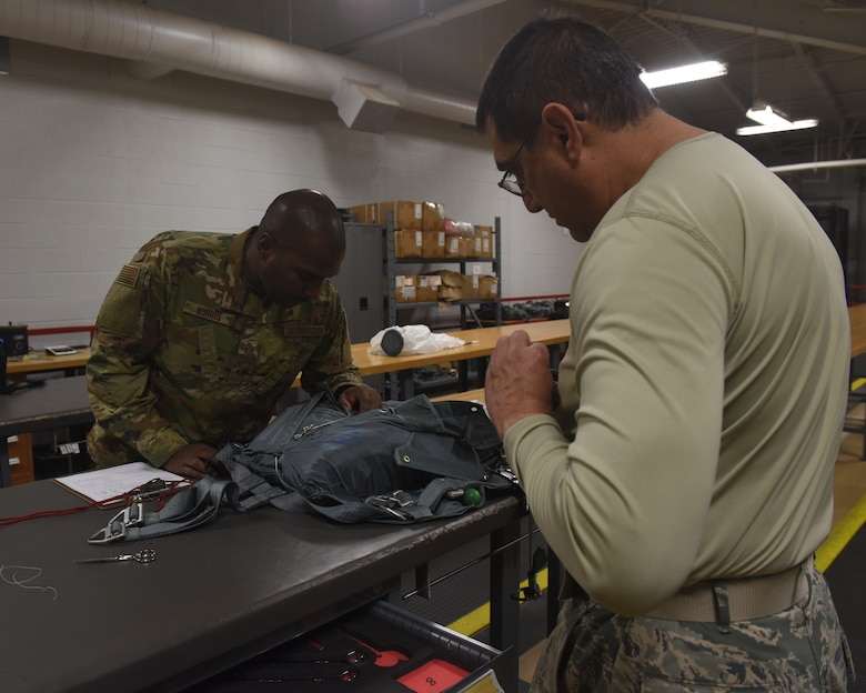 U.S. Air Force Tech. Sgt. Raymond Norris, left, 317th Operational Support Squadron aircrew flight equipment quality inspector, looks over a parachute being repacked by Master Sgt. Raymond Rosado, right, 103rd Airlift Wing AFE technician at Dyess Air Force Base, Texas, Dec. 12, 2018. The inspection cycles range from 30 days to a year, depending on the specific piece of equipment and how often it is used. (U.S. Air Force photo by Airman 1st Class Rebecca Van Syoc)
