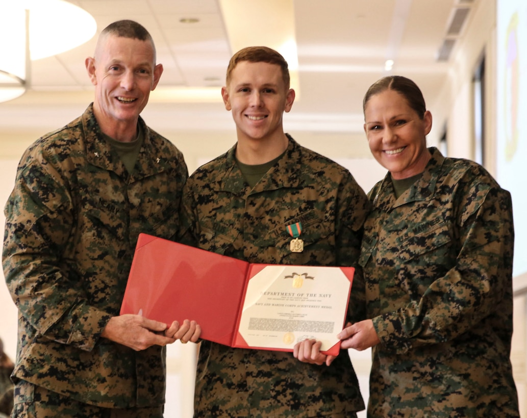 U.S. Marine Corps Brig. Gen. Stephen M. Neary, commanding general of 2nd Marine Expeditionary Brigade, and Sgt. Maj. Joy M. Kitashima of II Marine Expeditionary Force Information Group, presents a Navy and Marine Corps Achievement Medal to Lance Cpl. Matthew Ellis, a 2nd MEB intelligence specialist, at Camp Lejeune, N.C., Dec. 11, 2018. Ellis received the award for his exemplary performance while supporting the unit during Exercise Trident Juncture 18 in Norway. The award is earned by exemplifying superior performance outside one's designated military occupational specialty. (U.S. Marine Corps photo by Cpl. Patrick Osino)