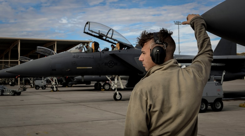 Airman 1st Class Clayton Ackerman, 757th Aircraft Maintenance Squadron (AMXS) Strike Aircraft Maintenance Unit F-15E Strike Eagle fighter jet maintainer, looks on as an F-15E prepares to launch Dec. 4, 2018 at Nellis Air Force Base, Nevada. The 757th AMXS participated alongside their pilots during the Weapons School Integration. (U.S. Air Force photo by Airman 1st Class Bailee A. Darbasie)