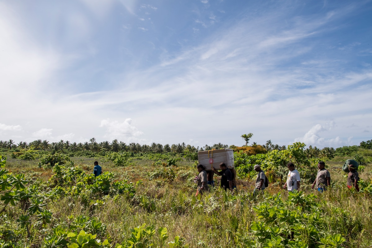 Fais Island locals carry supplies delivered to them during Operation Christmas Drop 2018.