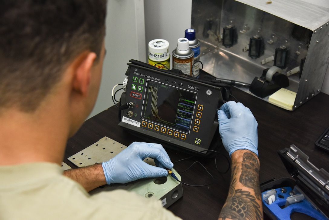 U.S. Air Force Airman Isaiah Edwards, 380th Expeditionary Maintenance Squadron non-destructive inspection technician, operates an ultrasonic transducer machine to find cracks in metal aircraft parts at Al Dhafra Air Base, United Arab Emirates, Dec. 7, 2018. The NDI shop uses certain techniques including fluorescent penetrant inspections and special oil analyses. These are some of the numerous methods used to repair, diagnose or prevent damage to the aircraft, its oil, and the parts. (U.S. Air Force photo by Senior Airman Mya M. Crosby)