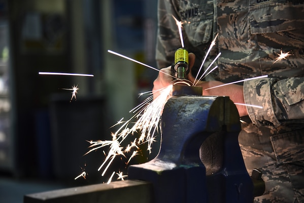 "U.S. Air Force Senior Airman Steven Schwab, 380th Expeditionary Maintenance Squadron aircraft structural repair technician, cleaning up the edge of a titanium metal piece at Al Dhafra Air Base, United Arab Emirates, Dec. 9, 2018. The fabrication flight, also known as ""fab flight"" or the ""American chopper of aircraft maintenance"" is comprised of Sheet Metals, Non-Destructive Inspection and Aircraft Structural Repair technicians. (U.S. Air Force photo by Senior Airman Mya M. Crosby)"