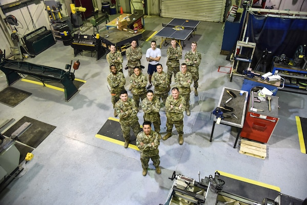 """The 380th Expeditionary Maintenance Squadron fabrication flight poses for a group photo at Al Dhafra Air Base, United Arab Emirates, Dec. 10, 2018. The fabrication flight, also known as """"Fab Flight"""" or the """"American chopper of aircraft maintenance"""" is comprised of Sheet Metals, Non-Destructive Inspection and Aircraft Structural Repair technicians. (U.S. Air Force photo by Senior Airman Mya M. Crosby)"""
