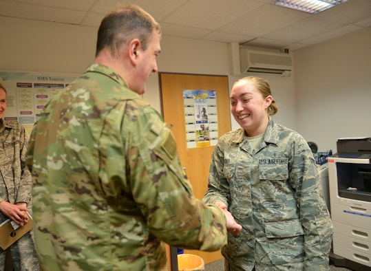 U.S. Air Force Brig. Gen. Mark R. August, 86th Airlift Wing commander, presents a coin to U.S. Air Force Airman 1st Class Sara Sparks, 86th Medical Support Squadron physical evaluation board liaison officer assistant, on Ramstein Air Base, Germany, Dec. 13, 2018.