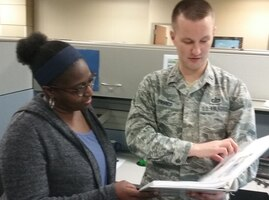 Paula Boykin and 1st Lt. Cory D'Amico review policy to increase Government Travel Card spending limits for people who evacuated from Tyndall Air Force Base due to Hurricane Michael. (U.S. Air Force Photo by Ed Shannon)