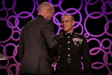 Brig. Gen. Ryan Heritage, the commanding general of Western Recruiting Region and Marine Corps Recruit Depot San Diego, presents Alan Knipe, Long Beach State University men's volleyball head coach, the 2018 United States Marine Corps American Volleyball Coach's Association NCAA Division 1-2 Men's National Coach of the Year Award during the AVCA 2018 National Convention in Minneapolis, Minnesota, December 13, 2018. The AVCA Convention gives the Marine Corps an opportunity to connect with more than 2,800 volleyball coaches who are members of the AVCA. (U.S. Marine Corps photo by LCpl Haley Gawronski)