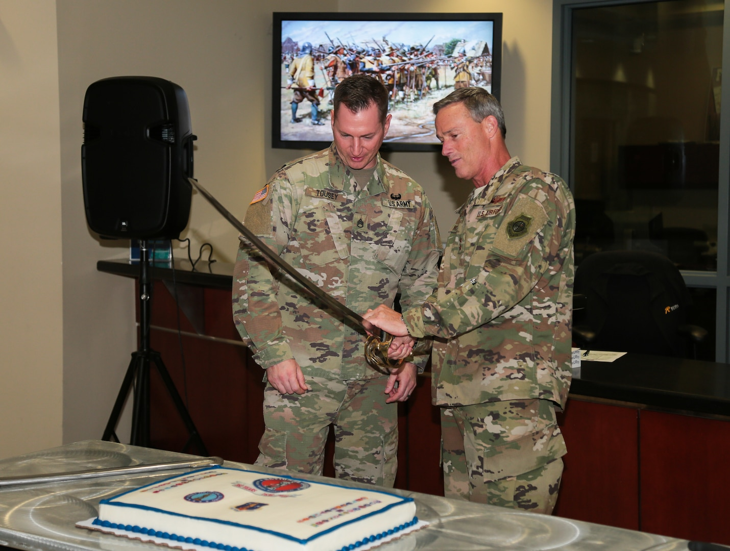 U.S. Air Force Maj. Gen. Jon K. Mott, , U.S. Central Command's director of exercises and training (right) and U.S. Army Staff Sgt. Michael Tousey (left) prepare to cut the cake to honor the National Guard's 382nd birthday at U.S. Central Command headquarters, Dec. 13, 2018. The National Guard administered State Partnership Program, established in 1993, is a key component of CENTCOM's mission and the National Defense Strategy. (U.S. Central Command Public Affairs photo by Tom Gagnier)