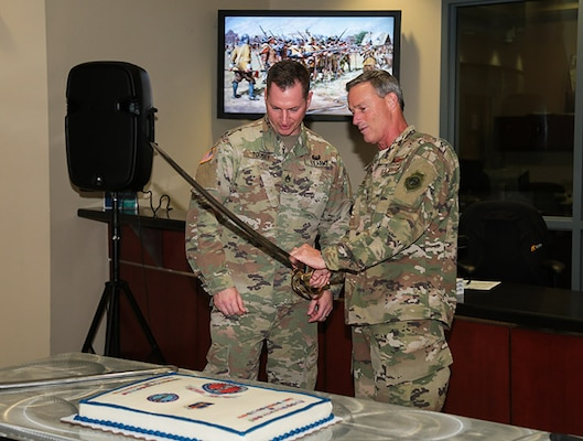 U.S. Air Force Maj. Gen. Jon K. Mott, right, U.S. Central Command's director of exercises and training, and U.S. Army Staff Sgt. Michael Tousey prepare to cut the cake to honor the National Guard's 382nd birthday Dec. 13, 2018. The National Guard-administered State Partnership Program, established in 1993, is a key component of CENTCOM's mission and the National Defense Strategy.