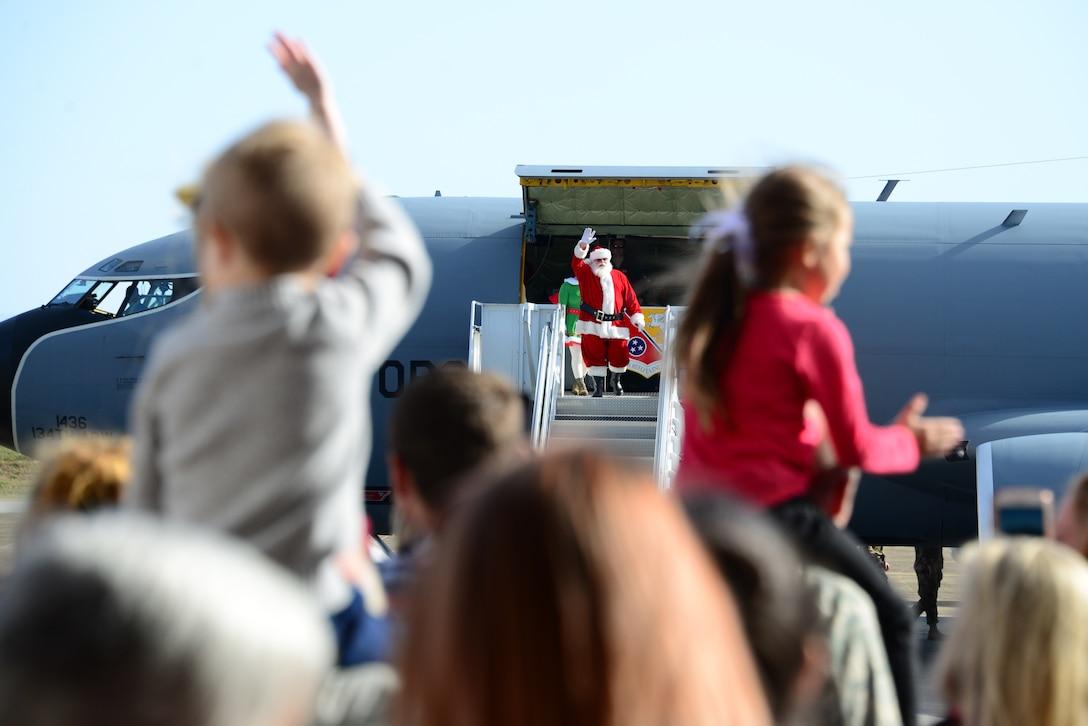 Santa walks out of a KC-135, waving