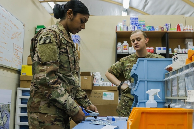 Missouri Army National Guardsmen, U.S. Army Sgt. Shelly Chadee, a healthcare noncommissioned officer assigned to Headquarters and Headquarters Company, 35th Combat Aviation Brigade, headquartered in Sedalia, Missouri, cuts medication packaging to fill a prescription for U.S. Army Cpl. Sara Coakley's, a healthcare specialist assigned to Headquarters and Support Company, 935th Aviation Support Battalion, headquartered in Springfield, Missouri, patient at the 935th ASB combined aid station, Camp Buehring, Kuwait, Dec. 10, 2018.  The CAS provided level-two medical care to U.S. Soldiers assigned to the 35th CAB.