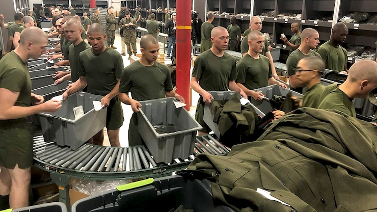 A room full of young men at boot camp is gathered along a conveyor belt with bins to receive dress uniforms.