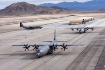 Three C-130 Hercules taxi the airfield as four MQ-9 Reapers wait under a sunshade at Creech Air Force Base, Nevada, Dec. 10, 2018. The base supported a Joint Forcible Entry exercise which integrates decisive action and demonstrates crisis response as well as global mobility. (U.S. Air Force Photo by Senior Airman James Thompson)