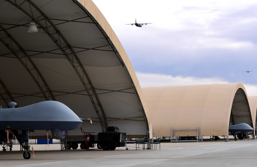 An MQ-9 Reaper waits under a sunshade while two C-130 Hercules takes off from Creech Air Force Base, Nevada, Dec. 10, 2018. The base supported a Joint Forcible Entry exercise which integrates decisive action and demonstrates crisis response as well as global mobility. (U.S. Air Force Photo by Airman 1st Class Haley Stevens)
