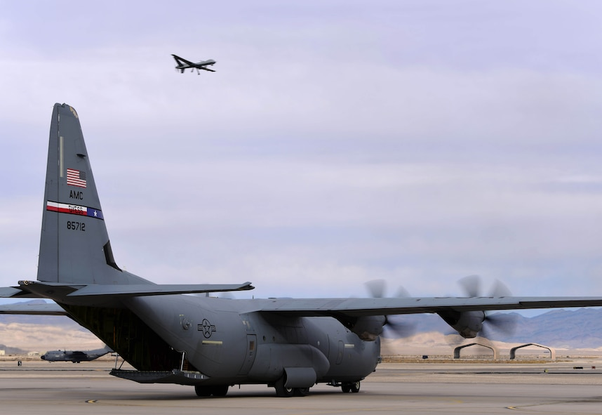 Two C-130 Hercules taxi the airfield at Creech Air Force Base, Nevada, Dec. 10, 2018, as an MQ-9 Reaper flies routine training missions. As one of the most challenging and complex missions of the year, Joint Forcible Entry exercise integrates decisive action and demonstrates crisis response as well as global mobility. (U.S. Air Force Photo by Airman 1st Class Haley Stevens)