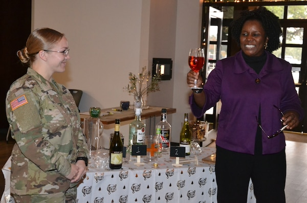 """Leslie Noel (right), Joint Base Substance Abuse Program prevention coordinator, demonstrates a standard drink of wine, which is actually water and red dye, that can be consumed in moderation during a talk she gave to military company-level commanders as part of """"The Gift of Presence: Resiliency Reset"""" event at the Vogel Resiliency Center at Joint Base San Antonio-Fort Sam Houston Nov. 30."""