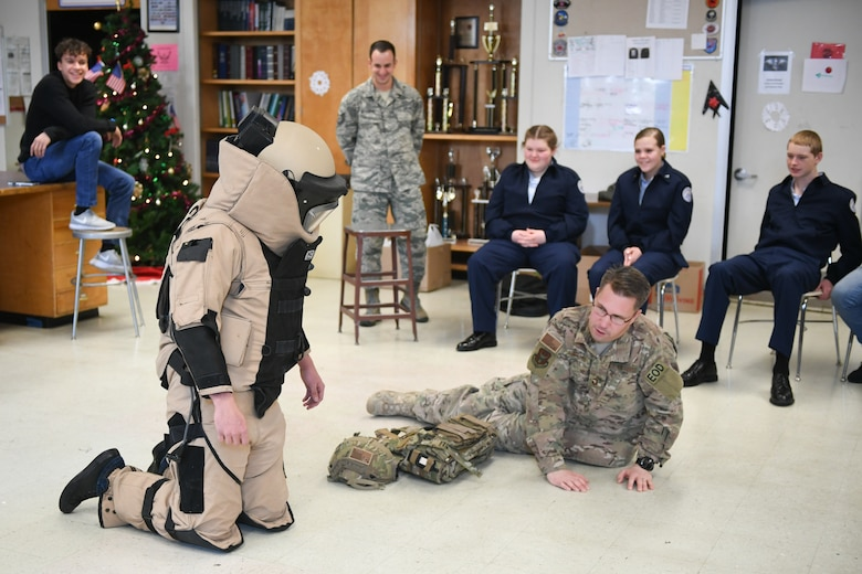 Senior Master Sgt. Eric Eberhard, 419th Explosive Ordnance Disposal Flight, has high school senior Calvin Kinnersley kneel while wearing a bomb suit. Technical Sgt. Andrew Mistkowski (back), 419th Fighter Wing recruiter, invited Hill Air Force Base EOD technicians to meet with Junior Reserve Officer Training Corps students at Clearfield High School in Clearfield, Utah, Dec. 12, 2018. (U.S. Air Force photo by Cynthia Griggs)