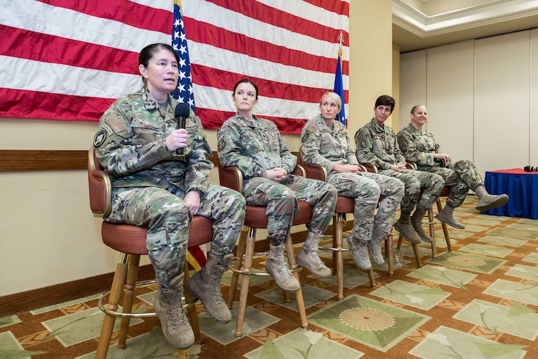 Five women speaking at a conference