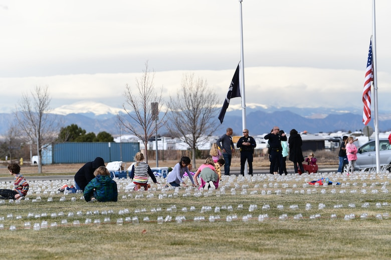 Students and teachers with a Cherry Creek Elementary School and the Aurora Police Department work together to set up luminaries to honor Colorado's fallen veterans at the Colorado Freedom Memorial in Aurora, Colorado, Nov. 28, 2018.