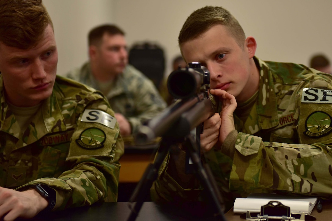 A man wearing the operational camouflage pattern uniform looks down the scope of a M24 sniper weapon system as a man wearing the OCP uniform watches him.