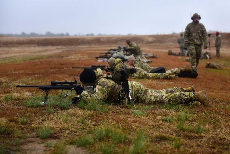 Men in military uniforms lay on ground looking down the scopes of M24 sniper weapon systems at a shooting range.