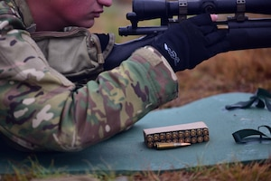 Bullets for a M24 sniper weapon system lay on a green mat as a man puts one into his M24.