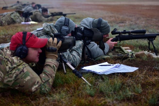 A man wearing  red hat and the operational camouflage pattern uniform looks down a scope at a range with two men wearing the Airman Battle Uniform.