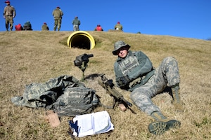 A man wearing the Airman Battle Uniform sits on a hill with a rifle, spotting scope, vest, backpack and clipboard.