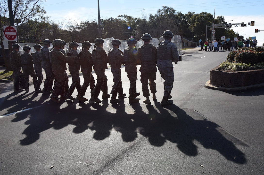 Members of the 81st Security Forces Squadron form a riot control team as they approach protestors during the 81st SFS protest drill at Keesler Air Force Base, Mississippi, Dec. 12, 2018. The scenario included peaceful protestors expressing their first amendment right that further escalated to a riot when they felt they weren't being heard. The drill, which was a joint effort with the Biloxi Police Department, was conducted to control or prohibit demonstrations and protests. (U.S. Air Force photo by Kemberly Groue)