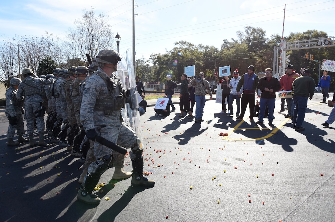 Members of the 81st Security Forces Squadron's riot control team hold the line while being assaulted by fruit thrown by protestors during a 81st SFS protest drill at Keesler Air Force Base, Mississippi, Dec. 12, 2018. The scenario included peaceful protestors expressing their first amendment right that further escalated to a riot when they felt they weren't being heard. The drill, which was a joint effort with the Biloxi Police Department, was conducted to control or prohibit demonstrations and protests. (U.S. Air Force photo by Kemberly Groue)